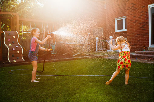 Two little girls playing with a hose.