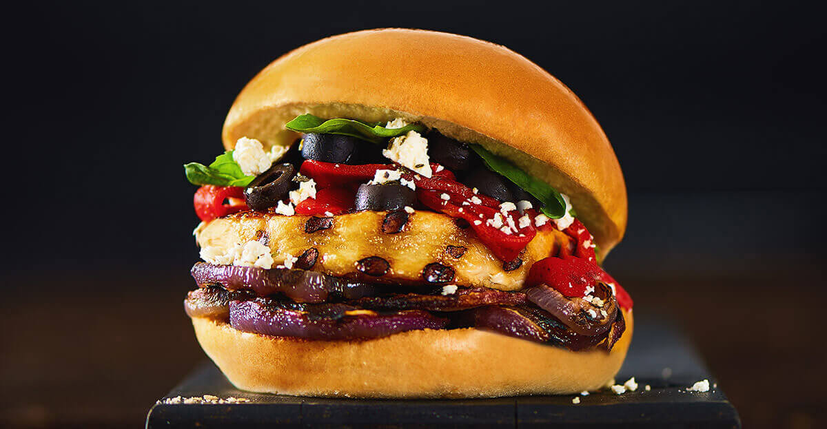 D'italiano Mediterranean burger pictured on a dark wooden cutting board infront of a black backdrop